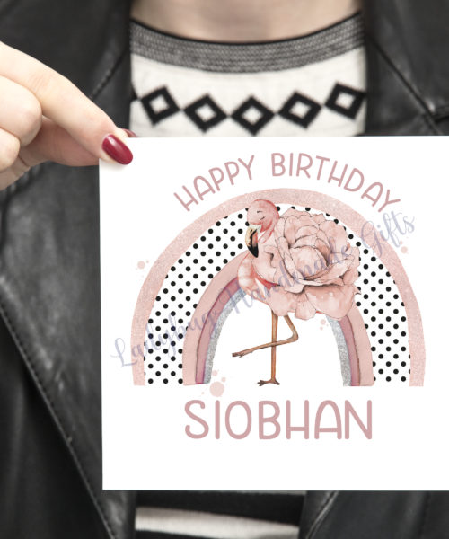 Lady holding birthday card with flamingo design