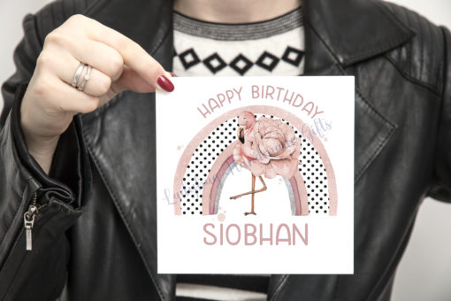 Lady holding birthday card with flamingo design